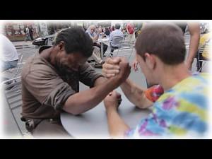 Dwóch bezdomnych siłuje się na rękę za pieniądze