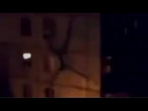 Kosmita wspina się po ścianie bloku