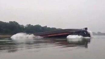 Przeładowana barka na rzece w Chinach