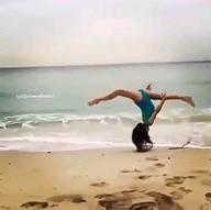 Kobieta w stroju kąpielowym na plaży popisuje się gibkością
