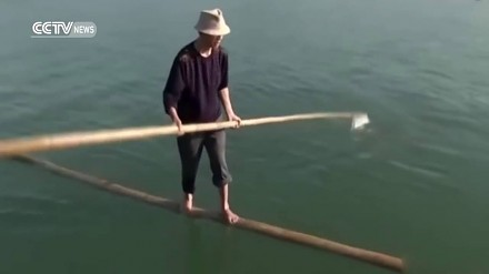 Chińczyk codziennie pływa do pracy na bambusowym patyku