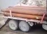 Rosjanie pakują ciężarówkę z rurami na barkę