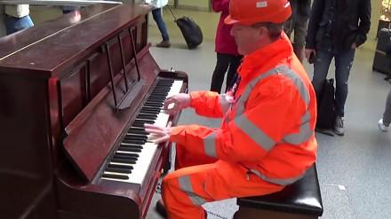 Robotnik wymiata na pianinie na dworcu