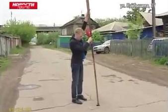Dziennikarz mierzy głębokość niepozornego uszkodzenia asfaltu