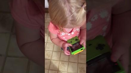 Dziewczynka próbuje swoich sił na gameboyu