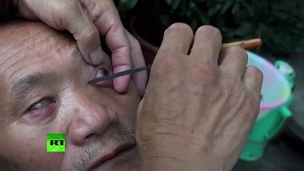 Chiński fryzjer używa noża do golenia oczu