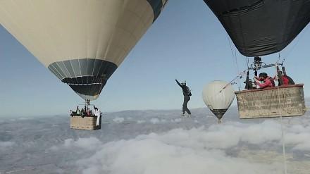 Próba przejścia po linie rozciągniętej między dwoma balonami
