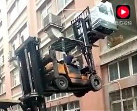 Załadunek drukarki za pomocą dwóch wózków widłowych