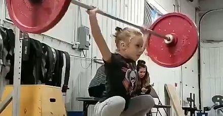 Mała dziewczynka podnosząca ciężary