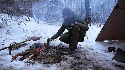 Survivalowy posiłek w lesie. Ogień na śniegu