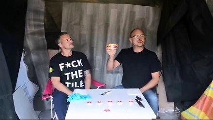 Dwóch twardzieli próbuje zjeść śledzia Surströmming
