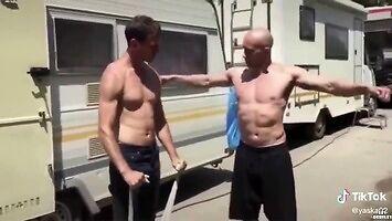 Łysy pokazuje koledze, jak prawidłowo ćwiczyć